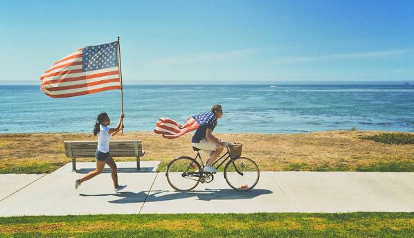 man wearing US flag riding a bike